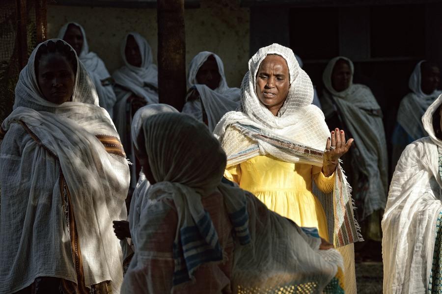 Alcune donne coperte da un velo bianco, pregano rivolgendo le mani al cielo